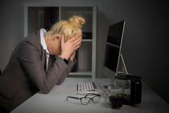 Deprimierte Frau im Büro, das ihren Kopf hält Lizenzfreie Stockfotos