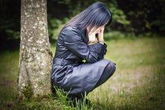 Deprimierte Frau im Fokus nahe Baum Stockfotos