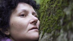 Deprimierte Frau im Wald, der auf einen Felsen mit Moos legt Stockfotografie