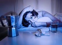 Deprimierte Frau in leidendem Kater des Betts nach der Parteinacht, die Wasserkaffee und -tabletten hat Stockbild