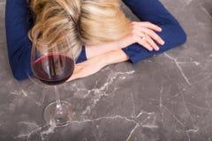 Deprimierte Frau mit dem Weinglas, das ihren Kopf auf Küchenarbeitsplatte stillsteht Stockbilder
