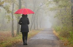 Deprimierte Frau mit rotem Regenschirm Lizenzfreie Stockfotos