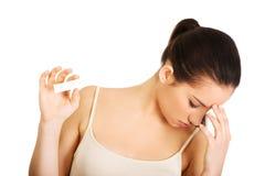 Deprimierte Frau mit Schwangerschaftstest Stockfoto