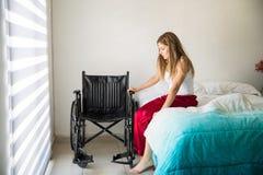 Deprimierte Frau nahe bei einem Rollstuhl Lizenzfreie Stockfotos