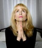 Deprimierte Frau sitzt auf dem Bettbeten Stockfotografie