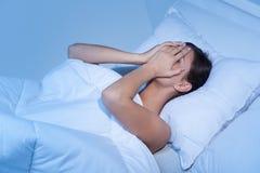 Deprimierte Frauen im Bett. Stockfotos
