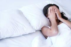 Deprimierte Frauen im Bett. Stockfotografie