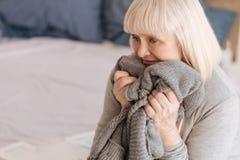 Deprimierte freudlose Frau, die eine gestrickte Jacke ihres Ehemanns hält Stockbilder