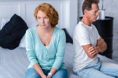 Deprimierte gealterte Paare, die auf dem Bett sitzen Lizenzfreies Stockfoto