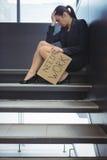 Deprimierte Geschäftsfrau, die auf der Treppe hält Pappblatt mit Textbedarfsarbeit sitzt Lizenzfreie Stockfotos