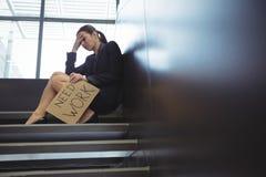 Deprimierte Geschäftsfrau, die auf der Treppe hält Pappblatt mit Textbedarfsarbeit sitzt Lizenzfreie Stockfotografie