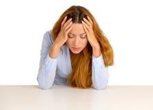 Deprimierte Geschäftsfrau, die auf einem Schreibtisch unten schaut sich lehnt Lizenzfreie Stockfotos