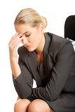 Deprimierte Geschäftsfrau, die auf Lehnsessel sitzt Lizenzfreie Stockfotos