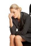 Deprimierte Geschäftsfrau, die auf Lehnsessel sitzt Lizenzfreie Stockbilder