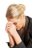 Deprimierte Geschäftsfrau, die auf Lehnsessel sitzt Stockfotografie