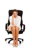 Deprimierte Geschäftsfrau, die auf Lehnsessel sitzt Lizenzfreie Stockfotografie