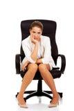 Deprimierte Geschäftsfrau, die auf Lehnsessel sitzt Stockfotos