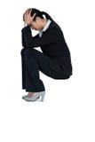 Deprimierte Geschäftsfrau, die auf Schritten mit der Hand auf Kopf sitzt Lizenzfreie Stockfotografie