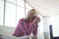Deprimierte Geschäftsfrau, die auf Sofa sitzt Lizenzfreie Stockbilder