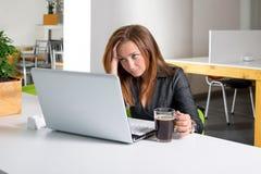 Deprimierte Geschäftsfrau, die am Computer sitzt Der müde und schläfrige Büroangestellte, der den Laptopschirm betrachten und der Stockbilder