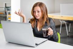Deprimierte Geschäftsfrau, die am Computer sitzt Der müde und schläfrige Büroangestellte, der den Laptopschirm betrachten und der Stockfoto