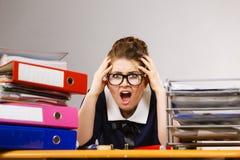 Deprimierte Geschäftsfrau, die am Schreibtisch sitzt Lizenzfreies Stockfoto