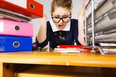 Deprimierte Geschäftsfrau, die am Schreibtisch sitzt Stockfotografie