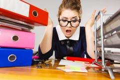 Deprimierte Geschäftsfrau, die am Schreibtisch sitzt Lizenzfreie Stockbilder