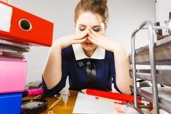 Deprimierte Geschäftsfrau, die am Schreibtisch sitzt Stockfoto