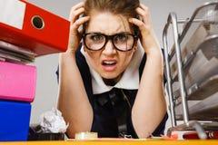 Deprimierte Geschäftsfrau, die am Schreibtisch sitzt Lizenzfreie Stockfotografie