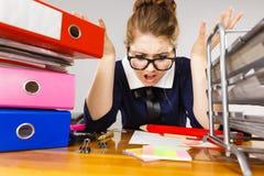 Deprimierte Geschäftsfrau, die am Schreibtisch sitzt Stockbilder
