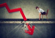 Deprimierte Geschäftsfrau, die unten dem fallenden roten Pfeil betrachtet lizenzfreies stockfoto