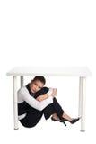 Deprimierte Geschäftsfrau, die unter einer Tabelle sich versteckt Lizenzfreie Stockbilder