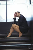 Deprimierte Geschäftsfrau mit der Hand auf ihrem Kopf, der auf Treppe sitzt Stockbilder