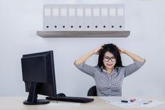 Deprimierte Geschäftsfrau mit einem Computer und einer Schreibarbeit Stockfoto