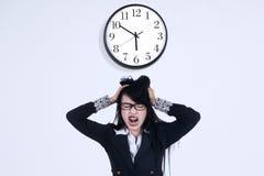 Deprimierte Geschäftsfrau mit einer Uhr Lizenzfreies Stockfoto