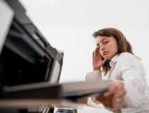 Deprimierte Geschäftsperson, die mit Drucker arbeitet Stockfotografie