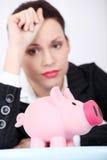 Deprimierte Geschäftsfrau, die ihre piggy Querneigung betrachtet. Lizenzfreie Stockfotos