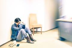 Deprimierte Hippie-Geschäftsfrau, die auf dem Büroboden sitzt lizenzfreies stockfoto