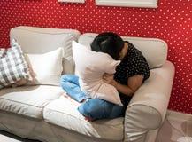 Deprimierte ihr Gesicht mit Kissen bedeckende und schreiende Frau Lizenzfreie Stockbilder