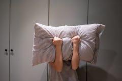 Deprimierte ihr Gesicht mit Kissen bedeckende und schreiende Frau Stockbild