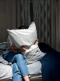 Deprimierte ihr Gesicht mit Kissen bedeckende und schreiende Frau Lizenzfreies Stockfoto