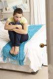 Deprimierte Jugendliche, die auf Bett sitzt Stockbilder