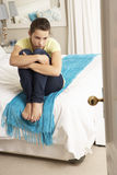 Deprimierte Jugendliche, die auf Bett sitzt Stockfotos
