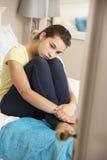 Deprimierte Jugendliche, die auf Bett sitzt Lizenzfreie Stockbilder
