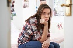 Deprimierte Jugendliche, die im Schlafzimmer sitzt Stockfotos