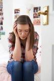 Deprimierte Jugendliche, die im Schlafzimmer sitzt Stockbild