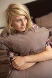 Deprimierte Jugendliche, die Kissen im Schlafzimmer umarmt Lizenzfreie Stockfotografie