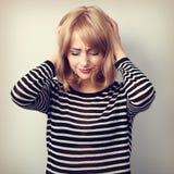 Deprimierte junge blonde Frau mit den Kopfschmerzen, die Kopf die Hände halten Stockfoto