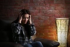Deprimierte junge Frau auf Ziegelsteinhintergrund Lizenzfreies Stockbild